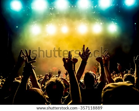 silhouettes of concert crowd in front of bright stage lights #357118889