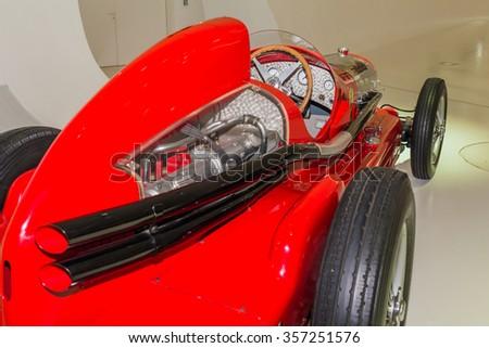 MODENA, ITALY - CIRCA APRIL 2015: Museum Enzo Ferrari Modena. Red Alfa Romeo Bimotore 1935 with the symbol of Alfa Romeo on. Side view. Rear wheel. #357251576