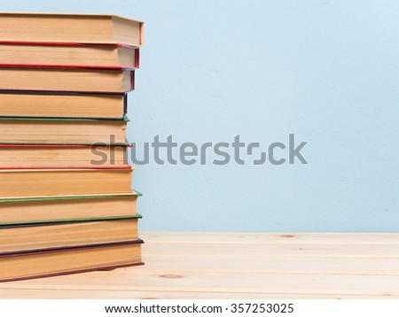Books on a wooden shelf on a blue background #357253025