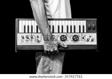 B&W man holding vintage studio keyboard synthesizer, isolated on black for music background Royalty-Free Stock Photo #357417761