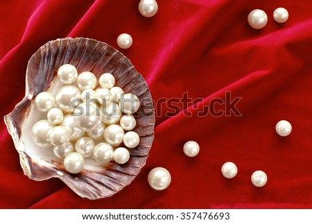 Shell with pearls on red velvet, top view