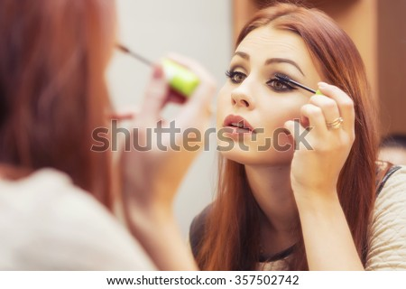 Brunette woman applying make up (paint her eyelashes) for a evening date in front of a mirror. Focus on her reflection Royalty-Free Stock Photo #357502742