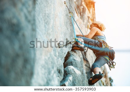 Adult female rock climber on vertical flat wall with poor relief - side view, close-up.  Royalty-Free Stock Photo #357593903