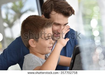 Little boy waving at tablet camera #357702758