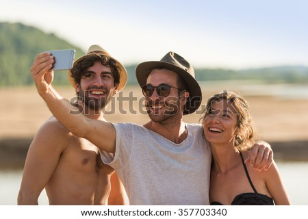 Three friends taking selfies at the beach. A woman wearing a bikini and two men with hats and sunglasses are having fun with a smartphone. They are looking at the screen for the picture.