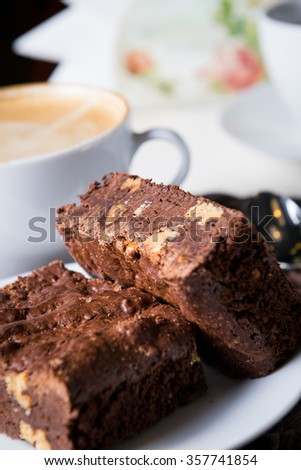 homemade chocolate brownies or chocolate cakes with nuts on white plate, cappuccino, close up #357741854