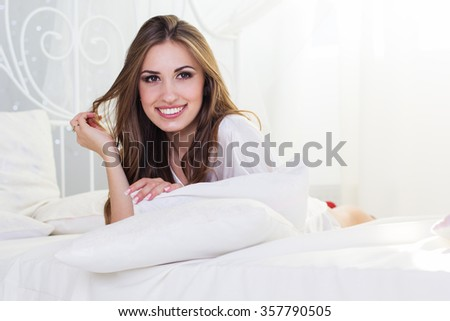 Pretty smiling girl is lying in bed with pillows #357790505