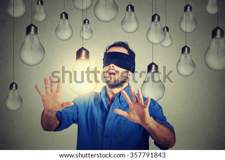 Blindfolded young man walking through light bulbs searching for bright idea  #357791843