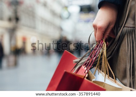 Closeup of woman holding shopping bags on the street with copy space #357891440