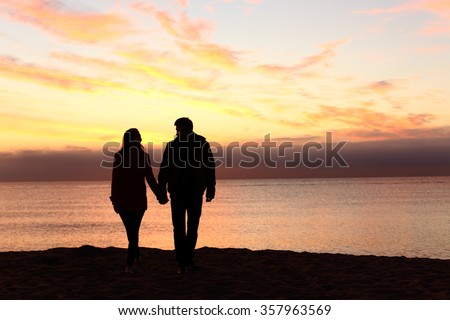 Front view of a full body of couple silhouettes holding hands and walking together looking each other in a date at sunset on the beach Royalty-Free Stock Photo #357963569