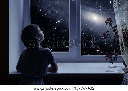 A little boy is standing near the window and looking outside, imagining boundless space with myriad of stars Royalty-Free Stock Photo #357969482