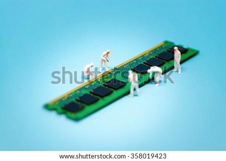 Miniature technicians repairing computer RAM module. Macro photo #358019423