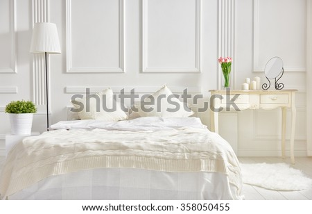 bedroom in soft light colors. big comfortable double bed in elegant classic bedroom #358050455