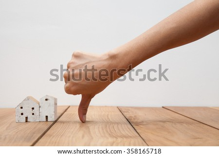 Real estate concept a hand showing thumb down at miniature house #358165718