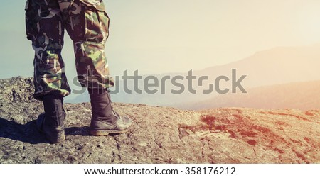 Soldier on the top of a mountain Royalty-Free Stock Photo #358176212