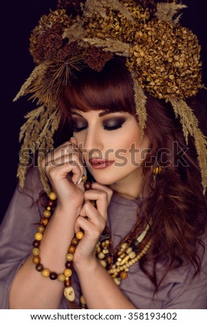 Beautiful young woman with dry flowers on head #358193402