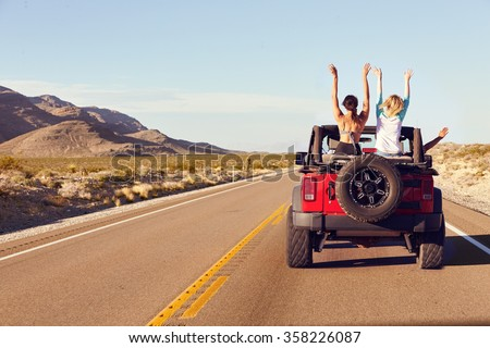 Rear View Of Friends On Road Trip Driving In Convertible Car Royalty-Free Stock Photo #358226087