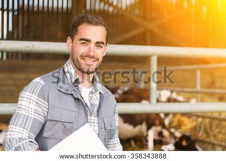 View of a Portrait of a Young attractive veterinary in a pasture with cows  #358343888
