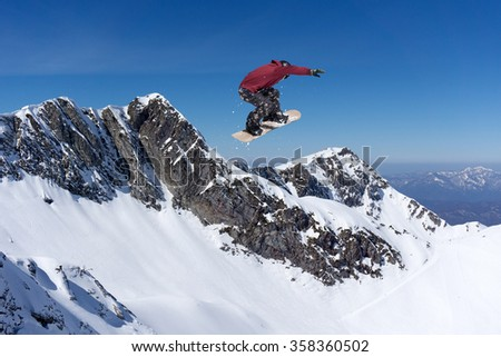 Flying snowboarder on mountains. Extreme winter sport. #358360502