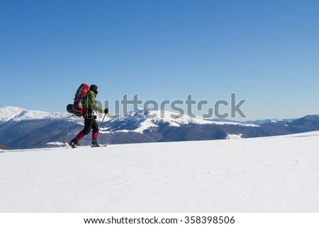 Winter hiking in the mountains on snowshoes with a backpack and tent. #358398506