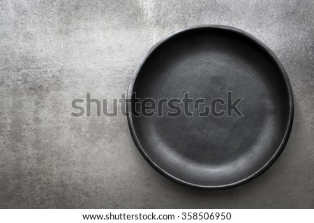 Empty rustic black plate over gray slate.  Aerial view, with copy space. Royalty-Free Stock Photo #358506950