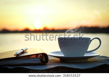 Silhouettes of sunrise morning coffee with a note and a pen Royalty-Free Stock Photo #358553537