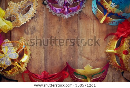top view of colorful Venetian masquerade masks on wooden table. retro filtered image