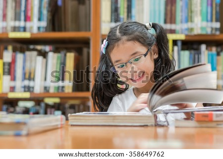 School education and literacy concept with Asian girl kid student learning or reading children's picture book in library or classroom