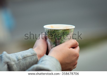 On the street the girl's hands with a cup of coffee