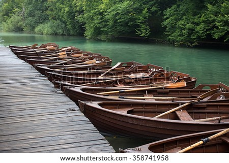 Photo closeup of row of identical wet wooden brown boats with oars mooring with chains at timber pier on beautiful riverscape background, horizontal picture