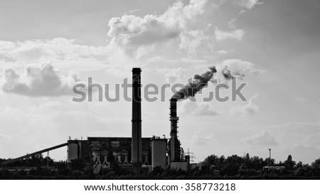 Smoking power plant black silhouette with cloudy sky on lake Bokod, Hungary, black and white image #358773218