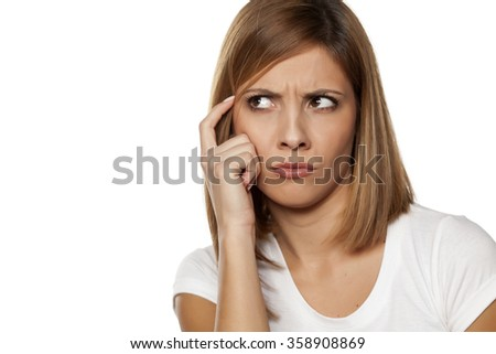 frowning young woman thinking with finger on forehead #358908869