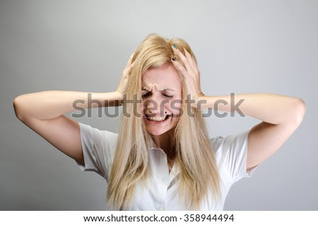 This is too loud! Frustrated young woman in formalwear holding head in hands and keeping eyes closed while standing against grey background #358944494