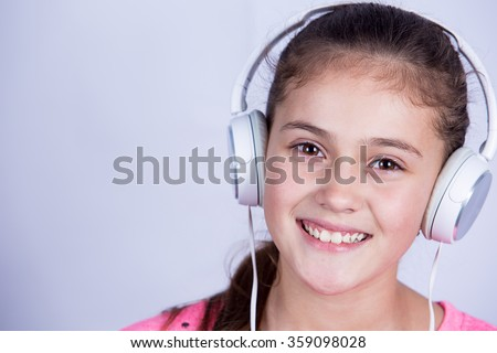 Smiling Little girl enjoying music in headphones at home relaxing. Relaxed little girl listening to music with earphones  looking serene and happy. #359098028