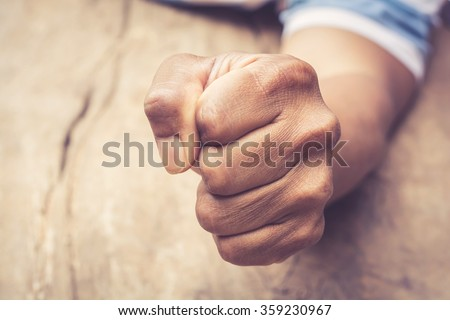 A man fists clenched on a wooden table in anger Royalty-Free Stock Photo #359230967