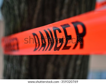 Danger Red Tape Warning in front of a tree/ Red Danger sign Tape Royalty-Free Stock Photo #359320769