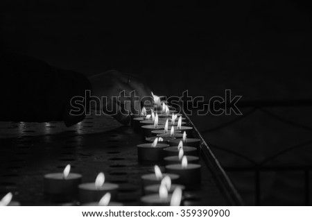 Candles and the hand putting a new candle. Aged photo. Black and white. #359390900