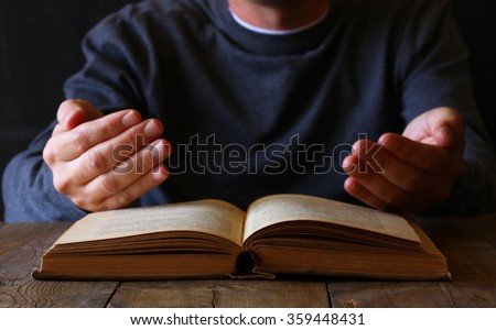 low key image of person sitting next to prayer book #359448431