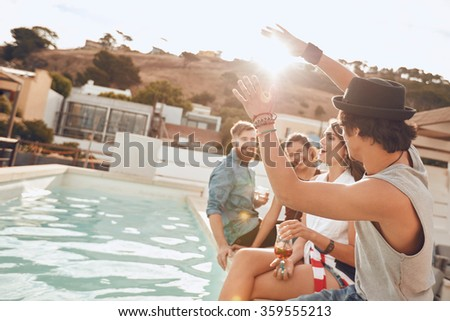 Young people sitting on the edge of the pool enjoying a party. Young woman singing during a the party. Multiracial friends having fun during rooftop party. #359555213