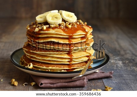 Pancakes with banana,walnut and caramel for a breakfast. Royalty-Free Stock Photo #359686436