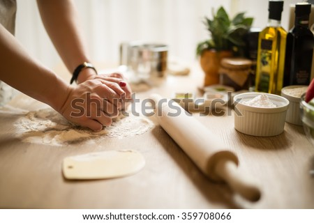 Woman cooking in the kitchen.Healthy food and lifestyle.Eating in.Cooking at home.Prepare dough for homemade whole grain bread.Woman kneading dough with her hands.Carbohydrates.Dieting Concept. Royalty-Free Stock Photo #359708066