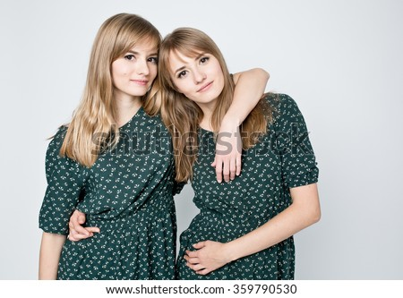 Beautiful two twins sisters together holding each other in hugs