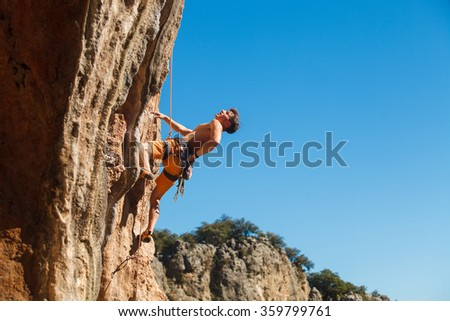 Rebelious rock climber on the wall against the blue sky - bold choice of real men. Dangerous adventure. Turkey, Geyikbayiri - Stock Image, Close-Up #359799761