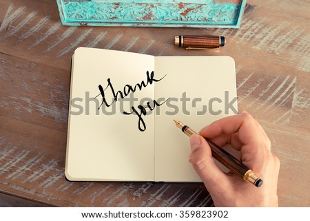 Retro effect and toned image of a woman hand writing a note with a fountain pen on a notebook. Motivational concept with handwritten text THANK YOU #359823902