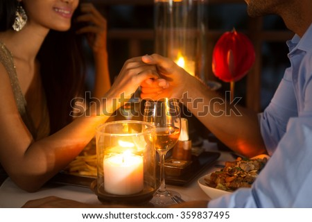 Romantic couple holding hands together over candlelight during romantic dinner  #359837495