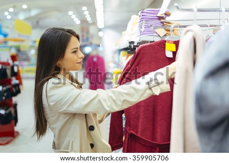 Beautiful woman glancing through clothes #359905706
