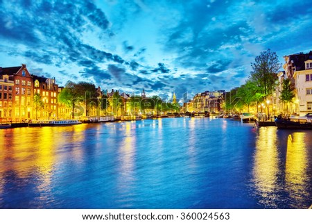 Famous Amstel river and night view of beautiful Amsterdam city. Netherlands #360024563