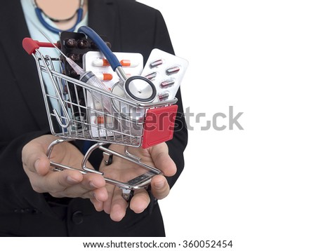 Female Doctor with black suit on white background. She's holding small shopping cart with colorful pills, syringe and stethoscope. Concept for health care costs or medical insurance. #360052454
