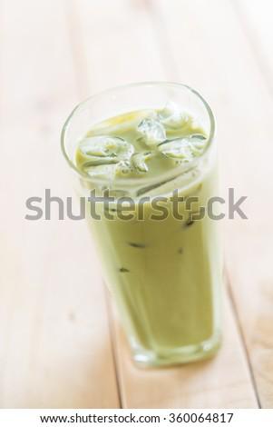 iced matcha latte on wood background #360064817