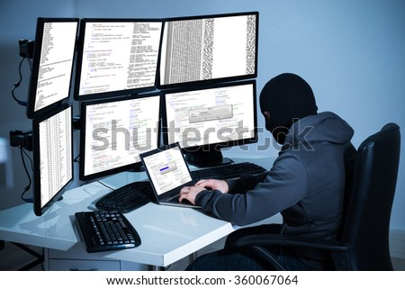 Male hacker using laptop against multiple monitors at desk in office #360067064
